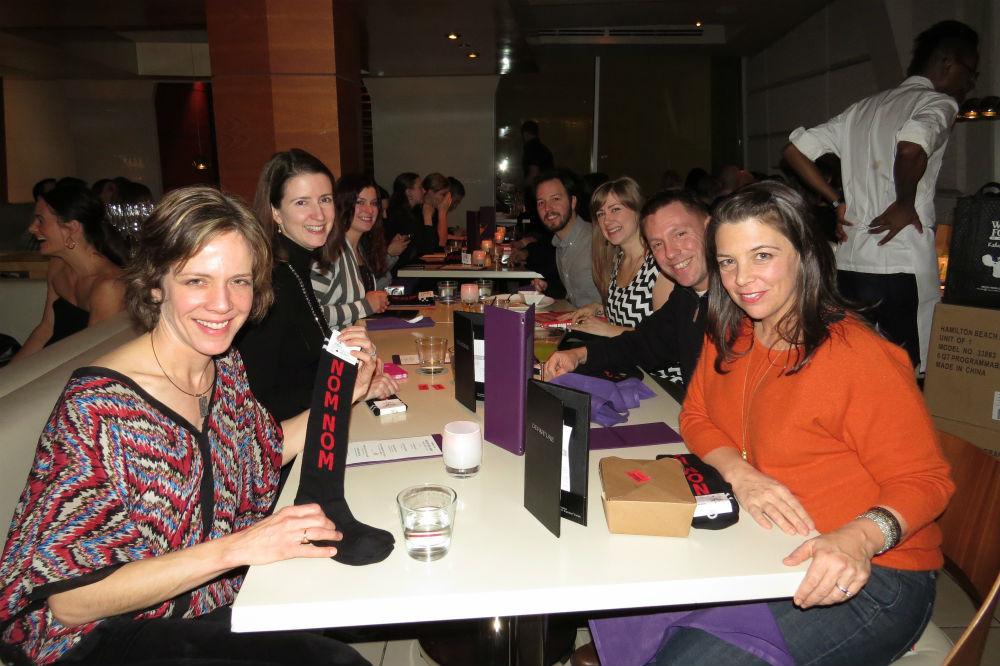 Smiling Restaurant goers holding up Nom Nom Paleo Socks at event with Nom Nom Paleo author