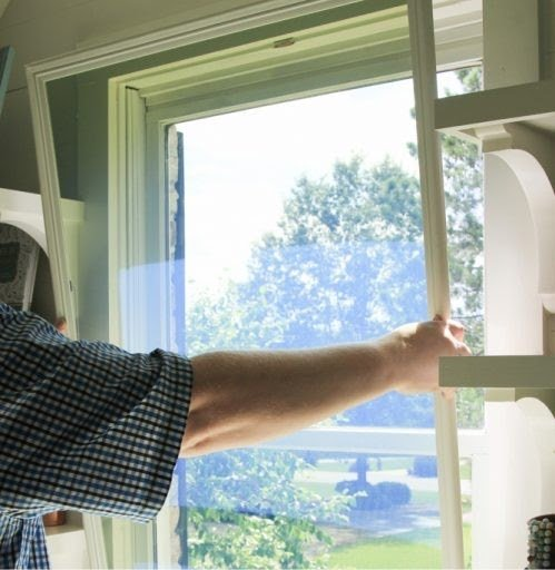 man installing window insert for diy window insulation