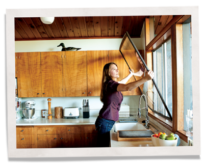 woman installing indow window insert for noise reduction and energy efficiency