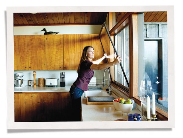 woman installing Indow window insert in kitchen window for bay area noise control