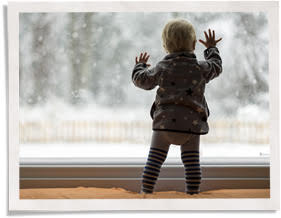 toddler touching window with insert installed because surface temperature is better controlled than with magnetic interior storm windows