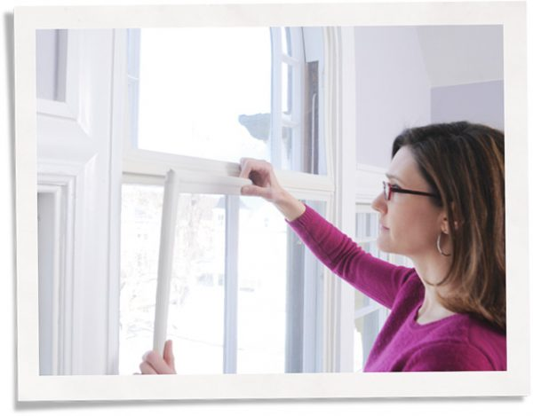 woman installing soundproofing window insert for apartment noise reduction