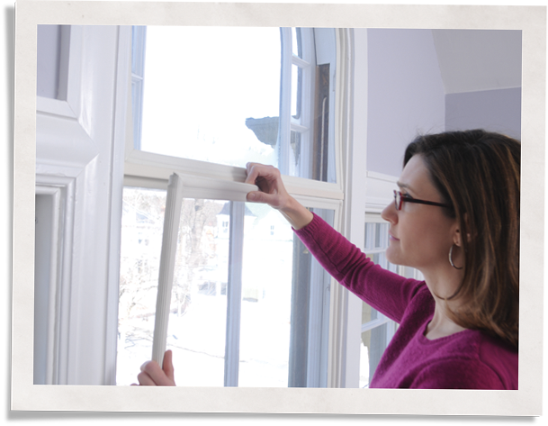 woman insulating home windows with Indow window inserts