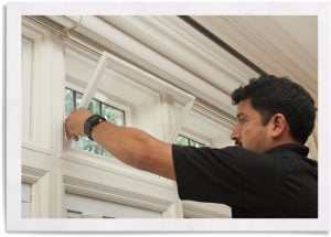 man installing Indow window inserts for winter house maintenance