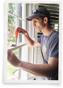 man weatherizing windows to block cold air