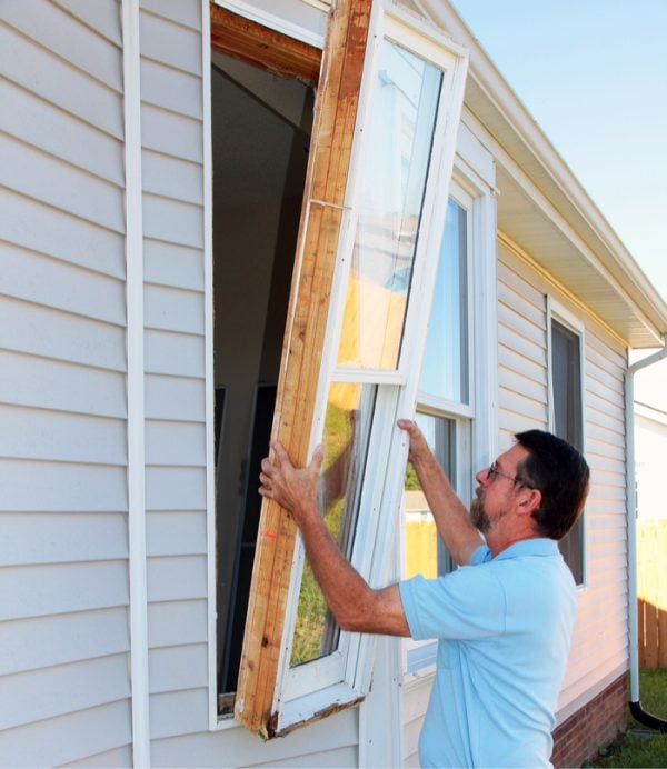 man replacing a window after a seal has broken and lost its energy efficiency