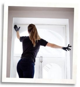 woman installing Indow insert for energy efficiency and added home value