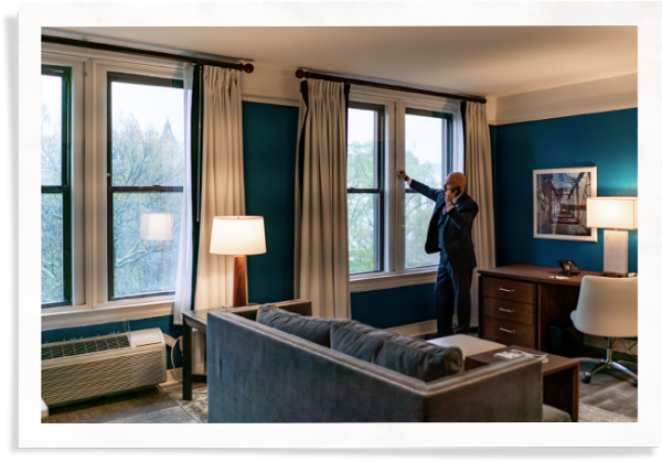 hotel guest in commonwealth hotel room leaning against window with Indow inserts used for hotel soundproofing