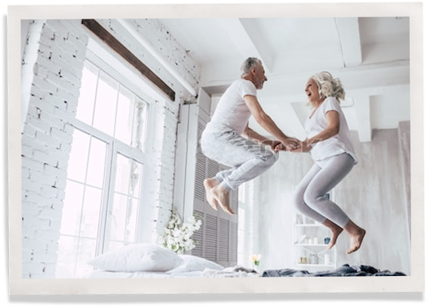 a man and woman jumping up and down on a bed next to a window
