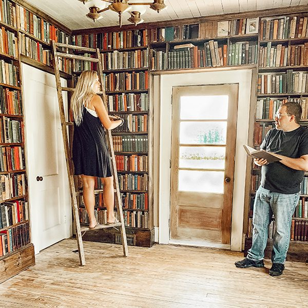 cozy old farmhouse library with woman on ladder and man with book standing across from her