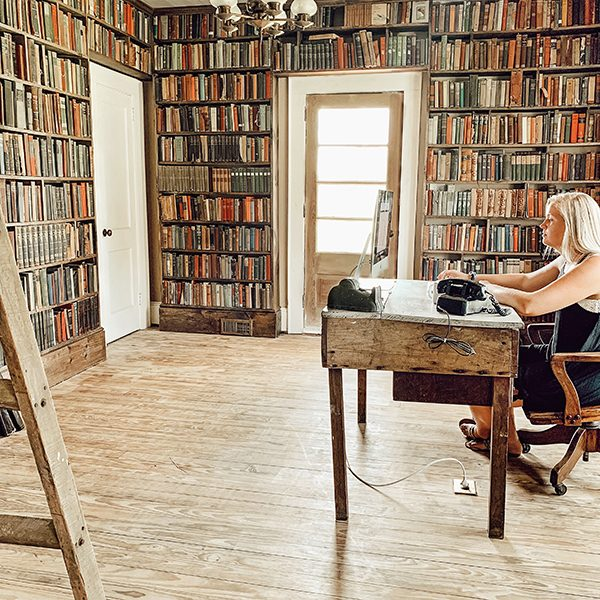 woman sitting at desk in remodeled old farmhouse library