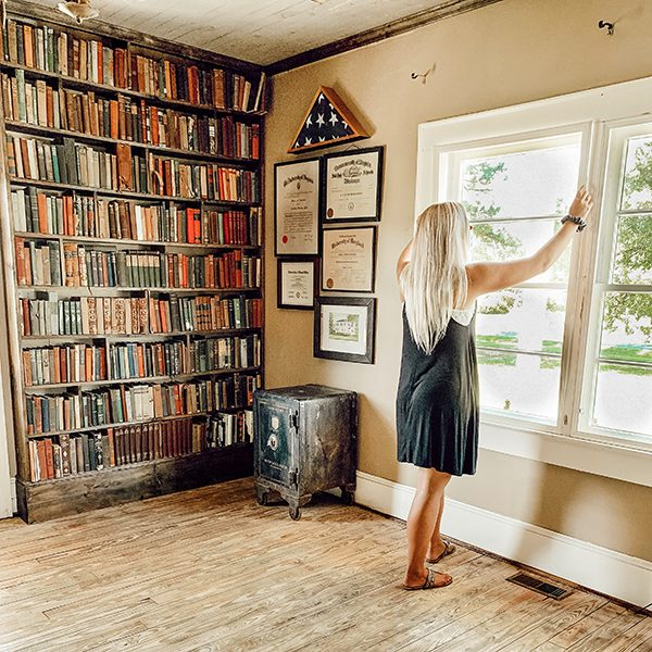 woman installing window inserts in remodeled old farmhouse library