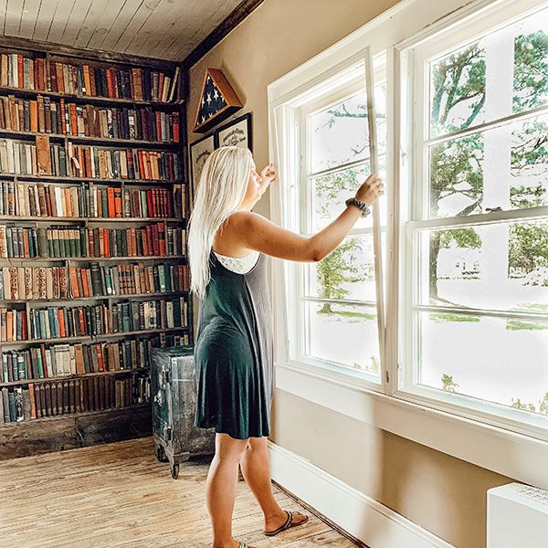 woman installing indow window insert into old farmhouse windows in library