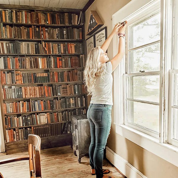 woman using laser tool to measure old farmhouse windows in library