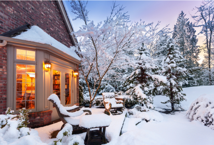 home covered in snow with warm, bright winterized windows