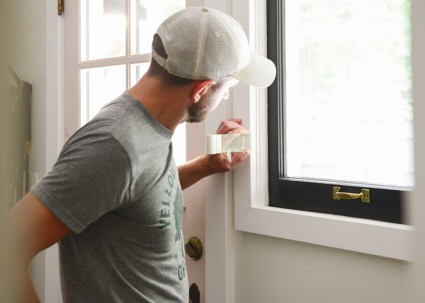 man measuring windows for window inserts for how to keep a mudroom warm