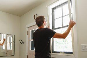 man installing window inserts to block city noise