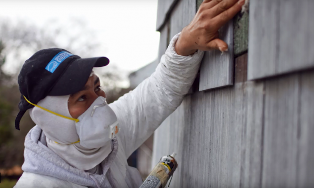 person with mask adding caulk to outside of home