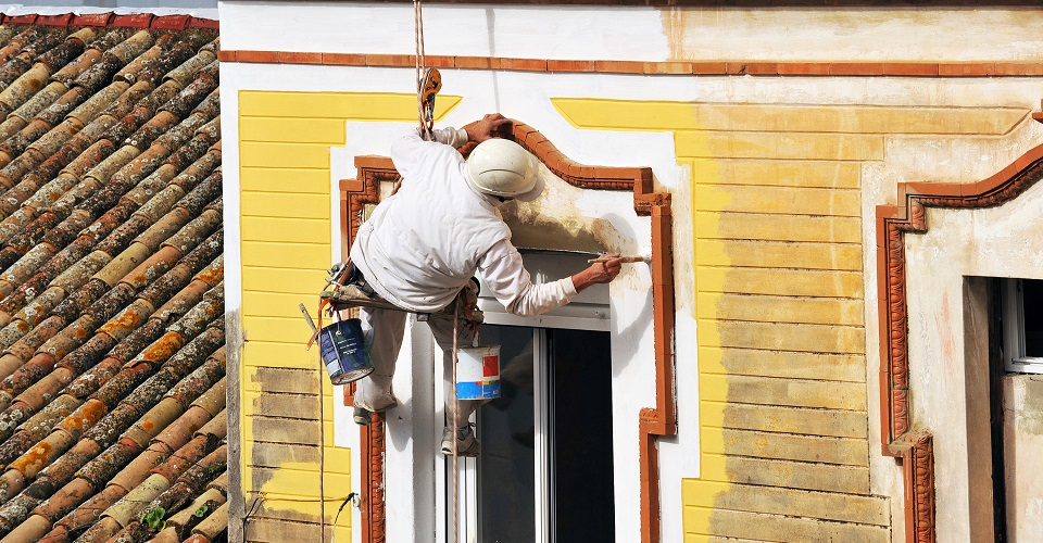 man painting historic home