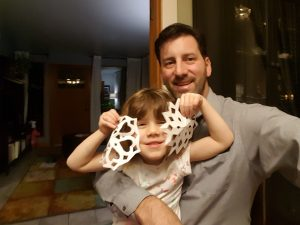 father and child creating holiday christmas window decorations - paper cut snowflakes