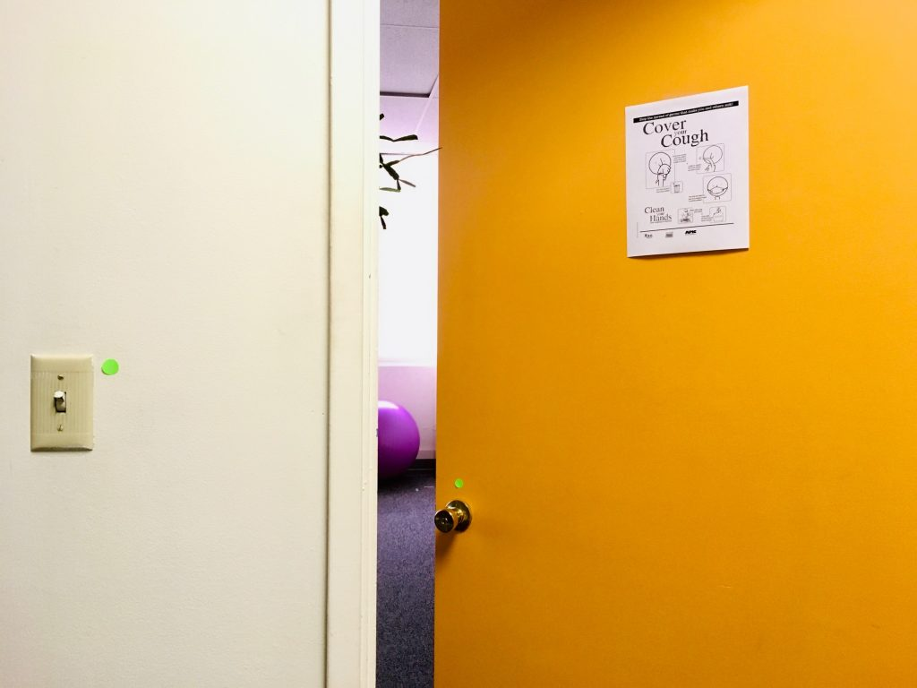 Door leading into office with sign posted containing hygiene information