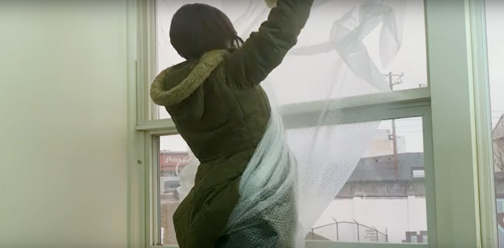 woman adding bubble wrap windows for insulation