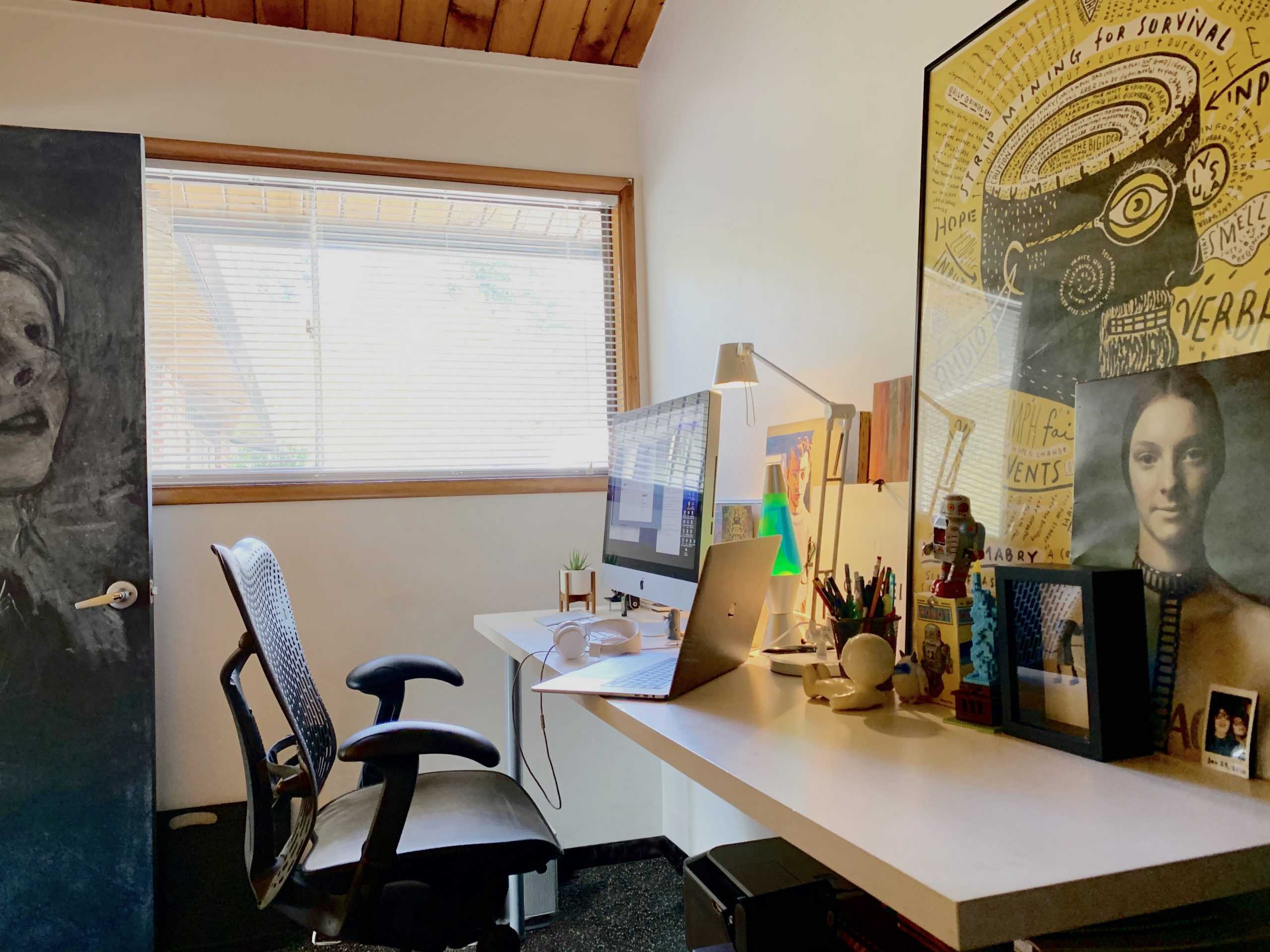 home office and dedicated work space with chair, large desk, two monitors, and large window
