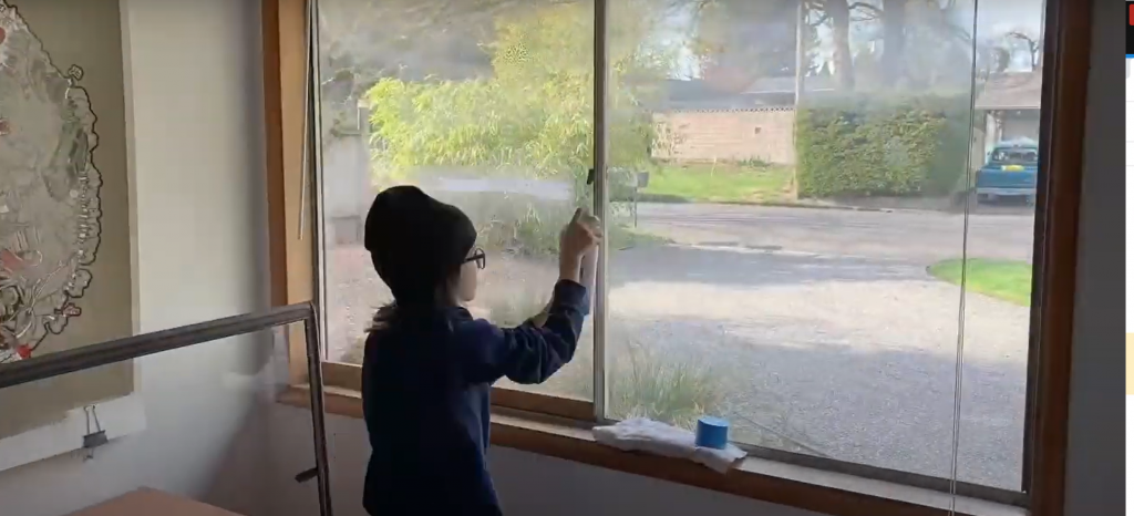child cleaning windows with window inserts for better air quality