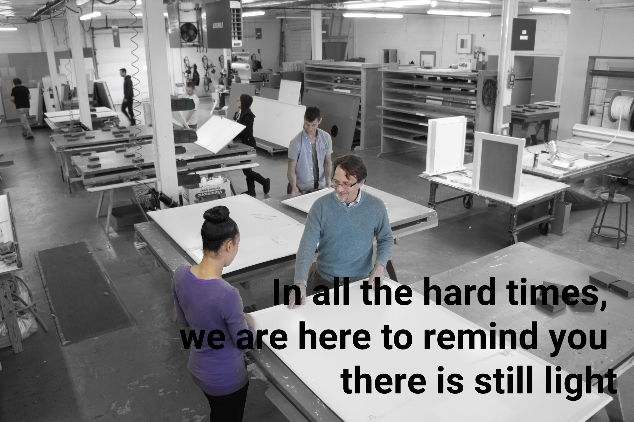 "factory workers smiling: text on image ""In all the hard times, we are here to remind you there is still light."""