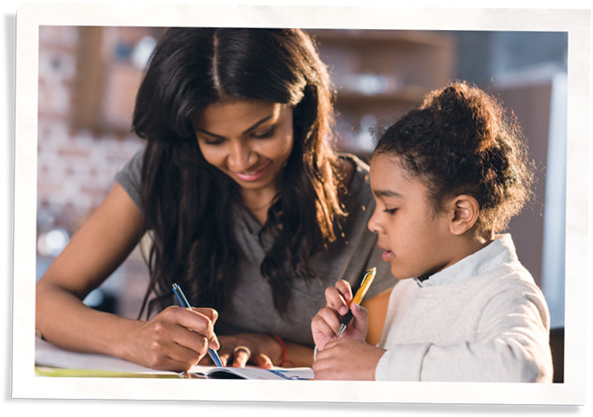 mother working with daughter on activity book that includes energy tips for kids