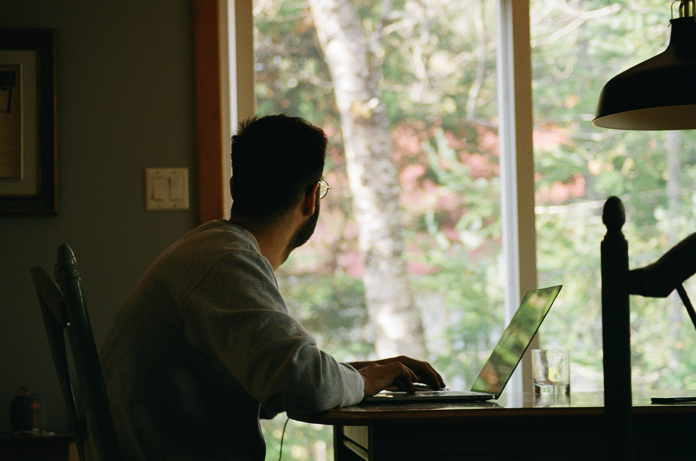 man sitting at a desk looking out the window