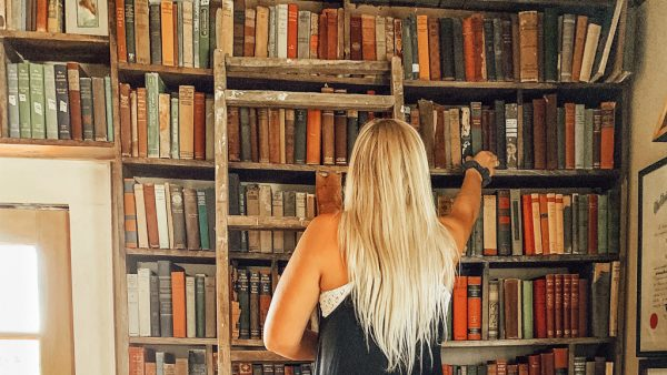 Woman reaching to a book in a home library