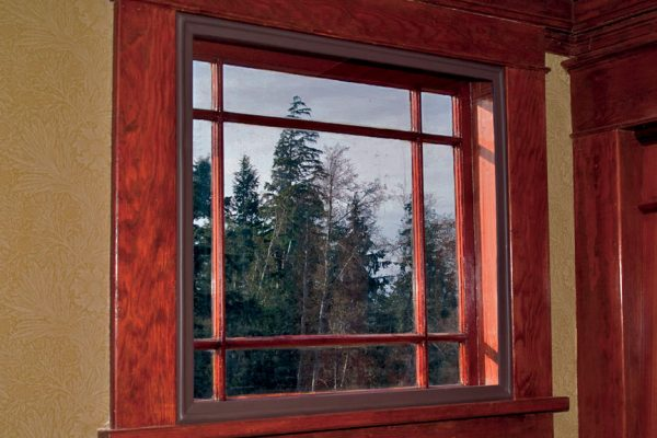 Wood-framed window with gray sky and trees outside and an Indow insert inside to create a seal in the window frame.