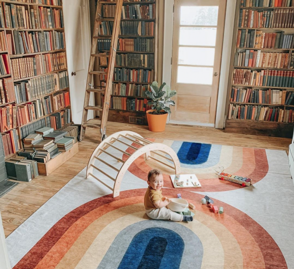 baby sitting on a rainbow rug in a play room