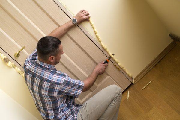 Man trimming foam insulation from around a door frame