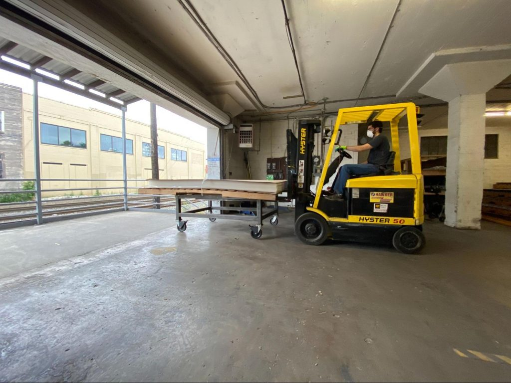 Indow production team member driving a forklift in a nearly empty Indow factory warehouse.