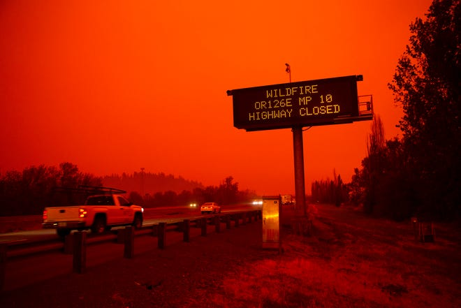 Cars on highway during Oregon wildfire evacuation with red sky and high closure alert sign.