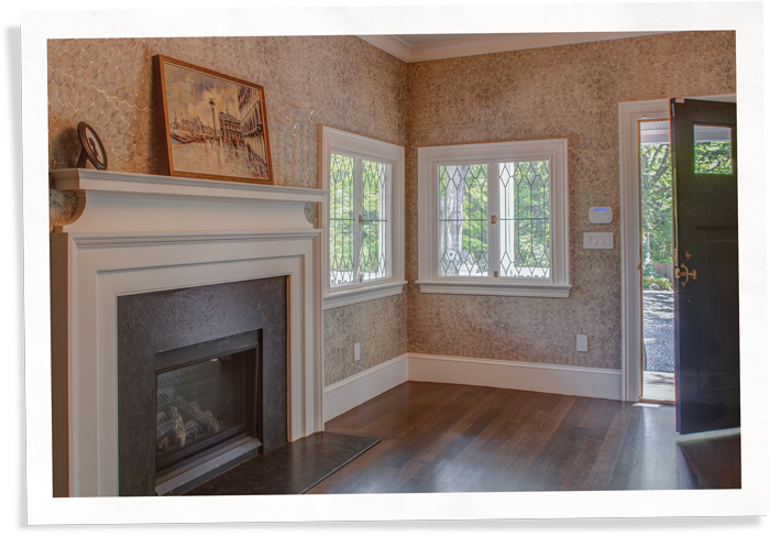 Shingle style house foyer with fireplace and Indow inserts in restored leaded glass windows (91)