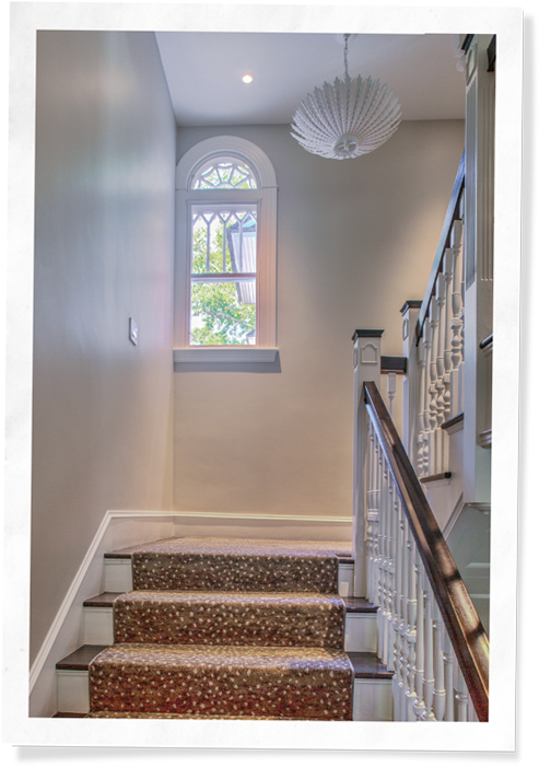 Restored staircase and arched window featuring Indow inserts in shingle style Cape Ann house (92)