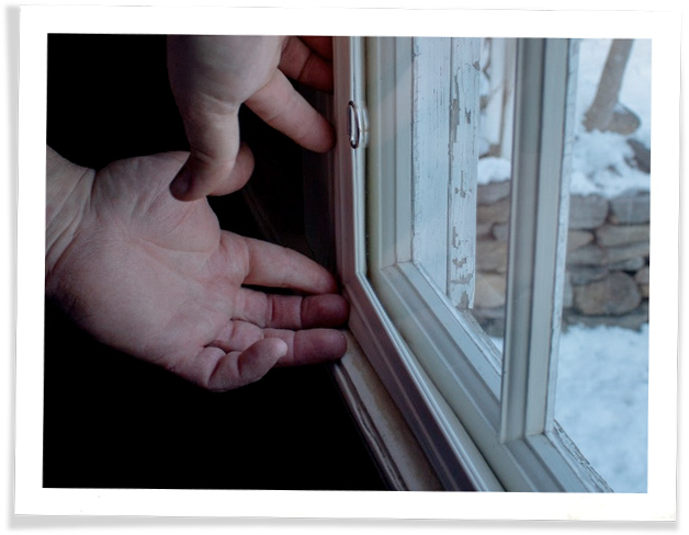 Adjusting the corner of an Indow insert: winter scene visible through acrylic insert & glass window.