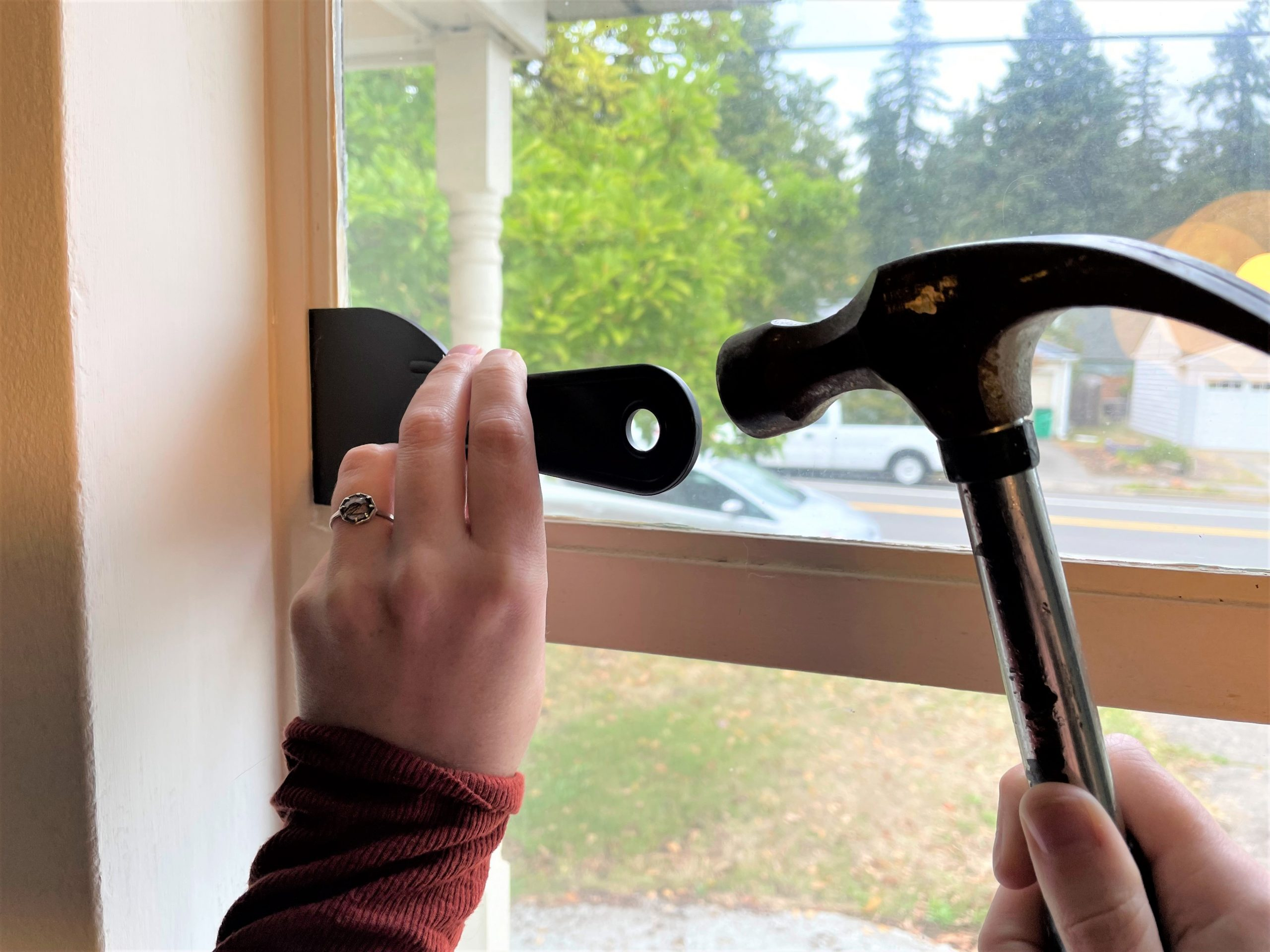 Hammering putty knife in a paint sealed crevice of a window painted shut